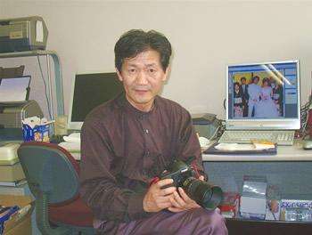 100万円以上もするという自慢のカメラを手にする山村安治社長