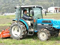 馬庭社長自らトラクターに乗り農作業をしている。